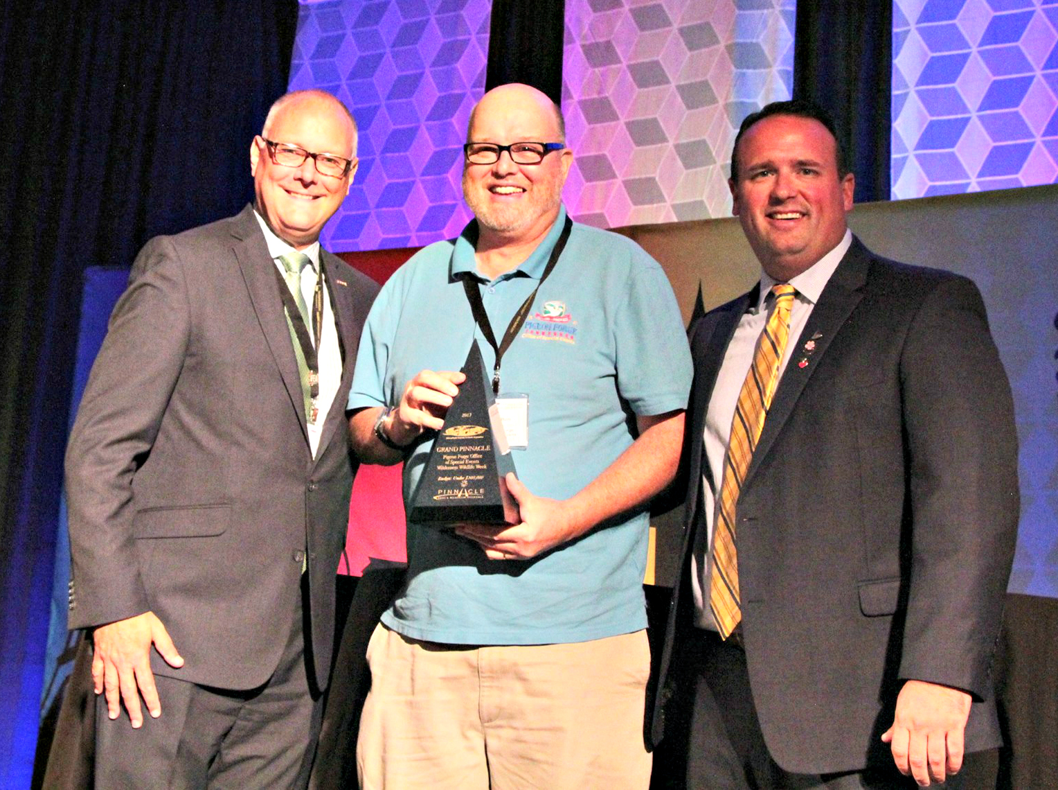 Stephen King, Des Moines Arts Festival executive director (left), and Andrew Vandepopulier, representing IFEA sponsor Haas & Wilkerson Insurance, congratulate Pigeon Forge Office of Special Events Manager Butch Helton on the city's second Grand Pinnacle Award for Wilderness Wildlife Week.